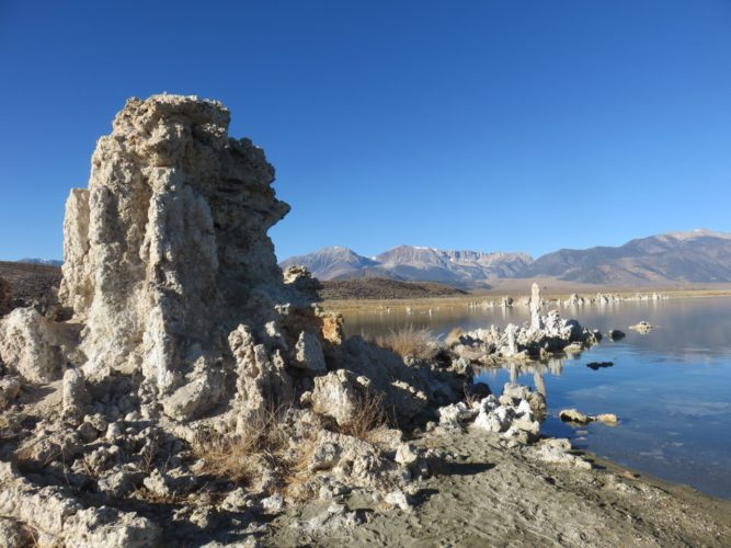 Mono lake with hoodoos plus mountains in background.